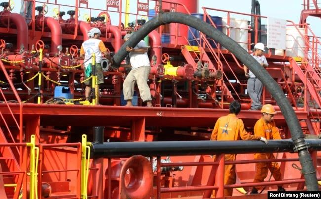 Pekerja memasang pipa untuk memompa minyak sawit mentah (CPO) ke kapal tanker di pelabuhan Belawan di Provinsi Sumatera Utara, 21 Februari 2013. (Foto: REUTERS/Roni Bintang)