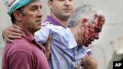 Δύο άνδρες απομακρύνουν τον οδηγό της αμαξοστοιχίας, Φρανσίσκο Χοζέ Γκαρζόν Άμο, από το σημείο του δυστυχήματος