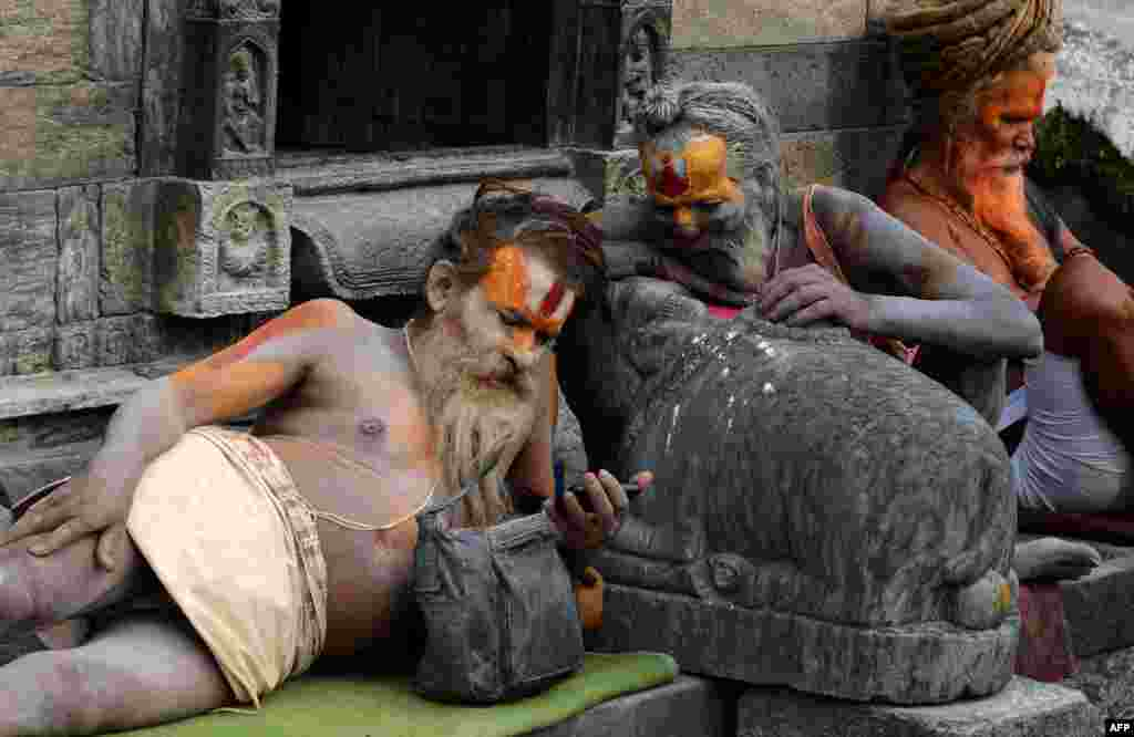 Hindu sadhus - holy men - watches a film on a mobile phone at the Pashupatinath Temple in Kathmandu, Nepal.