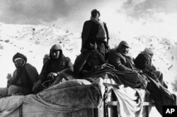 Afghan guerillas huddle together to stay warm while on a road in the mountains of Afghanistan in 1980.