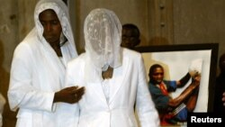 FILE - The wife, Marie-Louise Foe (C), and mother (L), of the late Cameroon player Marc-Vivien Foe, walk past his picture during his funeral ceremony.