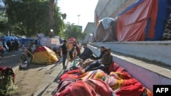 Iraqi anti-government protesters are pictured where they sleep on the side of a road in the Iraqi capital Baghdad's Tahrir square on November 20, 2019. - Protests erupted across Iraq in early October in fury over corruption, a lack of jobs and an…