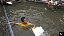 A Thai boy in a flooded area in Bangkok, Thailand. Hundreds of people died across Southeast Asia, China, Japan and South Asia in the last four months from prolonged monsoon flooding, typhoons and storms in October 2011.