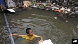 A Thai boy plays at a flooded area in Bangkok, Thailand. Hundreds of people have died across Southeast Asia, China, Japan and South Asia in the last four months from prolonged monsoon flooding, typhoons and storms, October 3, 2011.
