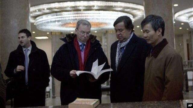Ketua Dewan Direksi Google, Eric Schmidt (kedua dari kiri), dan mantan gubernur New Mexico Bill Richardson (kedua dari kanan) melihat-lihat buku teks informasi teknologi di Pyongyang, Korea Utara (9/1). (AP/David Guttenfelder)