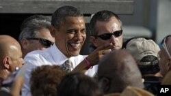 奥巴马总统在佛罗里达坦帕的一次竞选造势集会发表讲话后和支持者一道欢笑(2012年10月25日)。