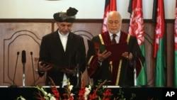 El presidente Ashraf Ghani Ahmadzai (izquierda) es juramentado por el juez Abdul Salam Azimi. Ghani ha firmado el esperado acuerdo de seguridad con EE.UU.
