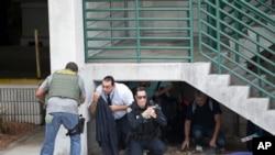 执法人员在佛罗里达州劳德代尔堡-好莱坞国际机场的停车场掩护民众。(2017年1月6日)