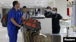 韩国检查员戴口罩在检查航班上抵达的乘客。