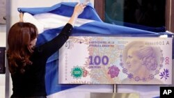 "Argentina's president Cristina Fernandez unveils the new 100-peso bill bearing the profile of former first lady Maria Eva Duarte de Peron, better known as ""Evita,"" at government palace in Buenos Aires, July 25, 2012."