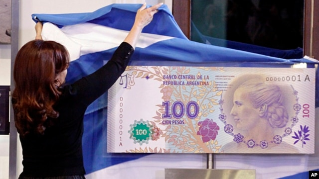 """Argentina's president Cristina Fernandez unveils the new 100-peso bill bearing the profile of former first lady Maria Eva Duarte de Peron, better known as """"Evita,"""" at government palace in Buenos Aires, July 25, 2012."""