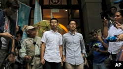 FILE - Pro-democracy activists Joshua Wong, center left, and Nathan Law, center right, walk out of the Court of Final Appeal Hong Kong, Oct. 24, 2017.