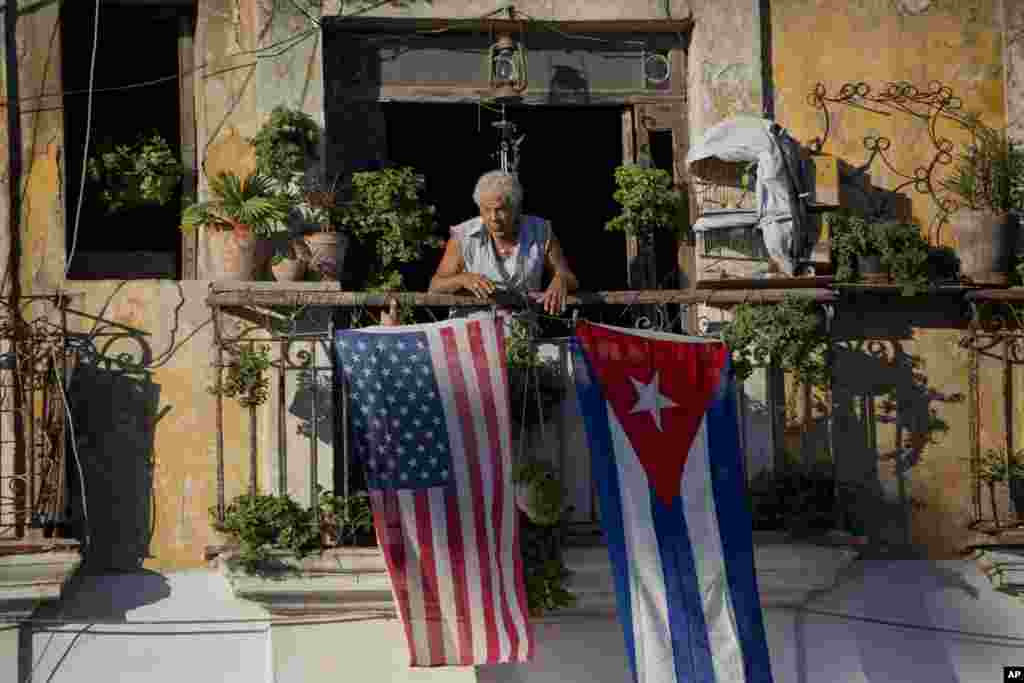 Javier Yanez stands on his balcony where he hung a U.S. and Cuban flag in Old Havana, Cuba. After the surprise announcement on Wednesday of the restoration of diplomatic ties between Cuba and the U.S., many Cubans said they hope it will mean greater access to jobs and help their struggling economy.