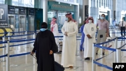 Penumpang Saudi mengantri untuk pemeriksaan suhu di terminal 5 di Bandara Internasional Raja Fahad, yang ditujukan untuk penerbangan domestik, di ibu kota Riyadh pada 31 Mei 2020. (Foto: AFP)