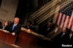 FILE - U.S. President Donald Trump is seen under the reflection of a House chamber railing as he delivers his State of the Union address to a joint session of the U.S. Congress on Capitol Hill in Washington, Jan. 30, 2018.