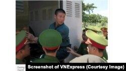 """Dương Văn Ngoan (giữa, bị còng tay) là một trong 9 người bị xét xử tại phiên tòa hôm 29/11 vì tội """"gây rối trật tự công cộng"""" do tham gia biểu tình chống dự luật đặc khu. (Ảnh chụp màn hình VNExpress)"""