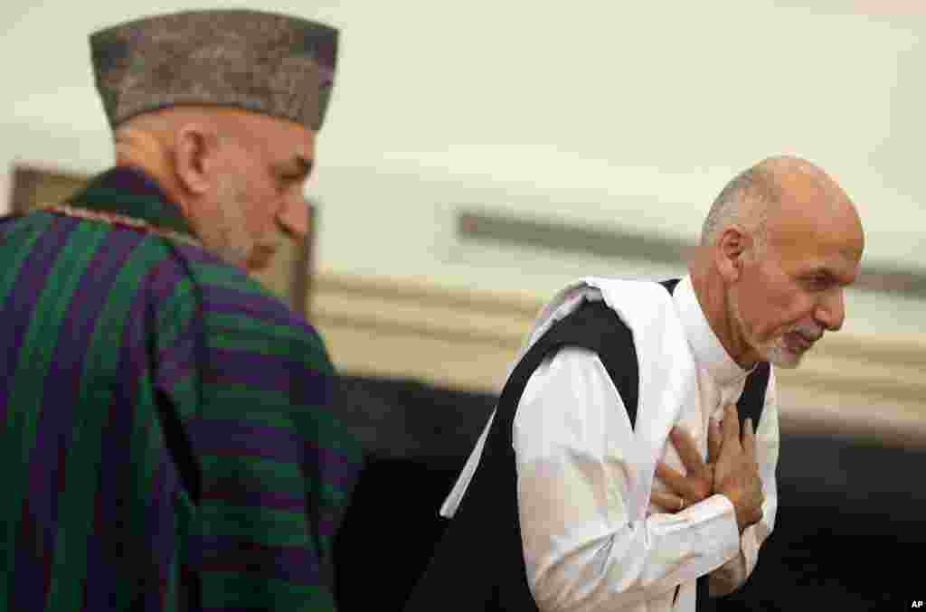 Ashraf Ghani Ahmadzai leaves after signing a power-sharing deal as president Hamid Karzai, left, stands at the presidential palace in Kabul, Afghanistan, Sept. 21, 2014.