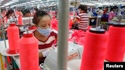 Người lao động làm việc tại một xưởng may ở ngoại ô Hà Nội. Nhiều nhà sản xuất nổi tiếng như Lever Style, có nhiều thân chủ có uy tín như nhãn hiệu Hugo Boss và J. Crew đã bắt đầu chuyển khâu sản xuất của họ từ miền Nam Trung Quốc sang Việt Nam trong mấy năm gần đây.