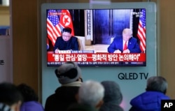 FILE - A TV shows a photo of U.S. President Donald Trump and North Korean leader Kim Jong Un, left, while people listen to Kim's New Year's speech, at Seoul Railway Station in Seoul, South Korea, Jan. 1, 2019.