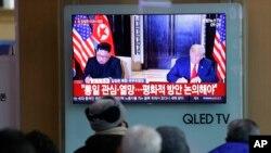 Sebuah acara TV memperlihatkan foto Presiden AS, Donald Trump, dan pemimpin Korut, Kim Jong Un, kiri, dan di saat yang sama tampak pemirsa menyimak pidato Tahun Baru Kim, di Stasiun Kereta Api Seoul, Korea Selatan, 1 Januari 2019 (foto: AP Photo/Ahn Young-joon)