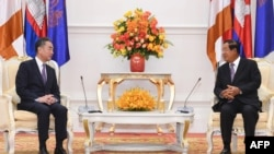 Cambodia's Prime Minister Hun Sen (R) speaks to China's Foreign Minister Wang Yi during a meeting at the Peace Palace in Phnom Penh on October 12, 2020.