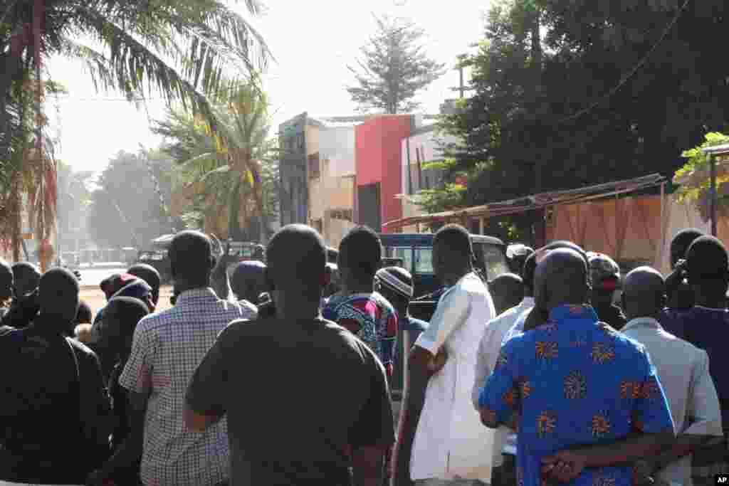 Pessoas assistem ao que se passa nos arredores do hotel Radisson Blu em Bamako