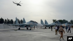 Russian Su-30 jets are parked at an airbase in Syria, on Oct. 22, 2015, as a Mi 24 helicopter gunship flies overhead.
