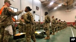 In this image provided by the U.S. Army, recent Army basic combat training graduates have their temperatures taken as they arrive at Fort Lee, Va, on March 31, 2020, after being transported using sterilized buses from Fort Jackson, S.C.