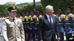 Menhan AS Chuck Hagel (kanan) berjalan berdampingan dengan Menhan Mesir Abdel-Fattah el-Sissi, dalam upacara menyambut kedatangan tamu negara di Kementrian Pertahanan Mesir di Kairo (24/3).