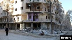 A man walks past damaged buildings in the rebel held besieged al-Sukkari neighbourhood of Aleppo, Syria, Oct. 19, 2016.