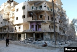 FILE - A man walks past damaged buildings in the rebel held besieged al-Sukkari neighbourhood of Aleppo, Syria, Oct. 19, 2016.