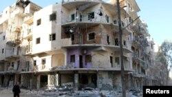 Seorang pria berjalan melewati bangunan yang roboh di kawasan al-Sukkari, Aleppo, Suriah (19/10). Rusia, Kamis (21/10) memerintahkan jeda kemanusiaan di Aleppo diperpanjang 24 jam.