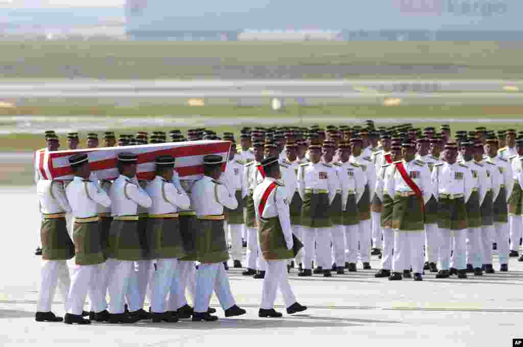 Malaysia Army soldiers carry a casket with one of the bodies from downed flight MH17 on arrival at Kuala Lumpur International Airport in Sepang, Malaysia. The bodies of 20 victims' of the ill-fated flight that was shot down over eastern Ukraine last month, returned home from Amsterdam.