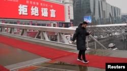 """一名男子走过北京一家墙上挂有""""拒绝谣言""""标语的商场。(2020年2月6日)"""