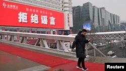Seorang pria berjalan di jembatan dekat sebuah pusat perbelanjaan di tengah merebaknya wabah virus corona di Beijing, China, 6 Februari 2020.