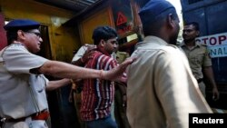 Police escort one of the four men convicted of raping a photojournalist outside a jail in Mumbai, March 21, 2014.