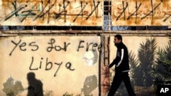 "A Libyan man walks past graffiti on a wall reading ""Yes for Free Libya"" in Benghazi, Libya, April 13, 2011"