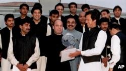 کرکٹ ورلڈ کپ 1992ء کی فاتح پاکستانی ٹیم کے کپتان عمران خان اس وقت کے وزیرِ اعظم میاں نواز شریف کی جانب سے دیے جانے والے عشائیے کے موقع پر انہیں ورلڈ کپ دے رہے ہیں۔ (فائل فوٹو)