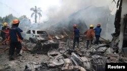 2015年6月30日救火人员在对坠毁的运输机引起的大火进行扑救。