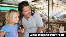 Farmer Ruth Mylroie witnesses a chicken laying an egg with a young visitor during a school tour of New Harmony Farm.