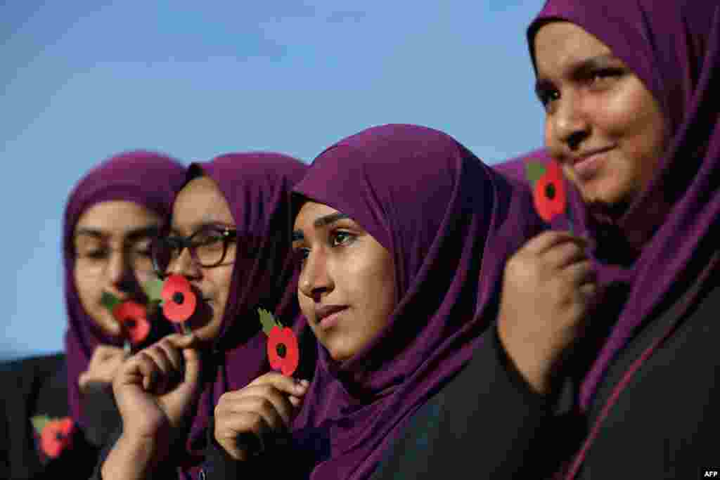 Pupils from Eden Girls' School hold poppies as they wait to observe a two minute silence in honour of Armistice Day in central London.
