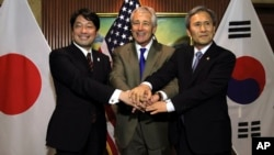 U.S. Secretary of Defense Chuck Hagel (C) poses with Japan's Defense Minister Itsunori Onodera (L) and South Korean Defense Minister Kim Kwan-jin (R) before their trilateral meeting on the sidelines of the International Institute for Strategic Studies Sha