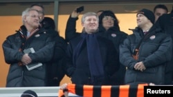 FILE - Rinat Akhmetov is seen flanked at a soccer match by Sweden's Foreign Minister Carl Bildt (L) and Poland's Foreign Minister Radoslaw Sikorski (R) Nov. 23, 2011, in Donetsk, Ukraine.