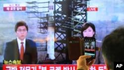 Seorang warga Korsel menggunakan telepon pintarnya untuk memotret siaran televisi yang memberitakan peluncuran roket Korea Utara di Stasiun Kereta Api di Seoul, Korsel (12/12).