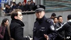 中國警察在2011年2月27日在上海和平劇院附近要求採訪'茉莉花遊行的外國記者離開。(資料圖片)