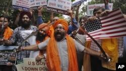 Miembros del Akali Dal, un partido político sij, muestran espadas y letreros de protesta en Nueva Delhi