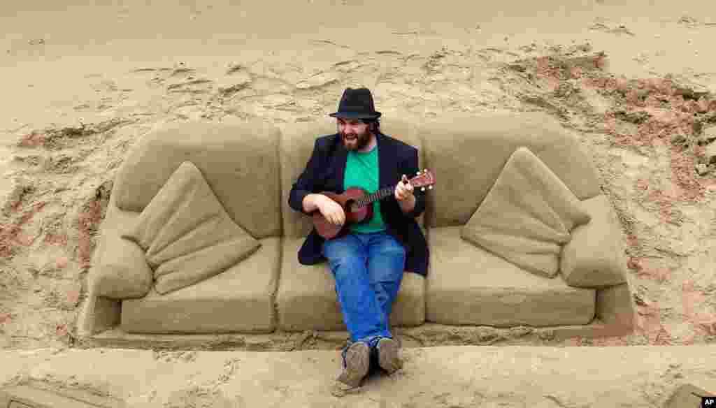 លោក Luc Valvona ច្រៀងចម្រៀងដោយមានលេងឧបករណ៍តន្រ្តី ukulele ខណៈពេលលោកអង្គុយលើសាឡុងដែលធ្វើឡើងដោយដីខ្សាច់នៅតាមបណ្តោយច្រាំងទន្លេ Thames ក្នុងទីក្រុងឡុងដ៍ កាលពីថ្ងៃទី២៣ ខែឧសភា ឆ្នាំ២០១៥។