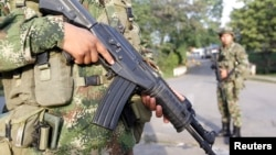 FILE- Colombian soldiers stand guard o a street in Caloto, Columbia, Feb. 6, 2014.