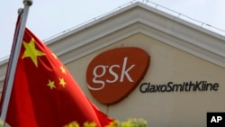 FILE - A Chinese flag is hoisted in front of a GlaxoSmithKline building in Shanghai, China. Police accused Peter Humphrey, a British executive of drug maker GlaxoSmithKline, on May 14, 2014, of leading a sprawling scheme to bribe doctors and hospitals to