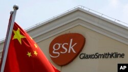 FILE - In this July 24, 2013 file photo, a Chinese flag is hoisted in front of a GlaxoSmithKline building in Shanghai, China.